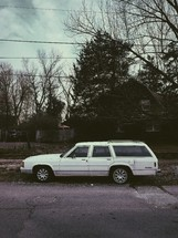 a station wagon parked in front of a house