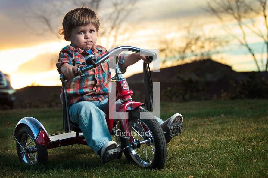 Toddler boy riding red tricycle on grass with mountains and trees in background at sunset.