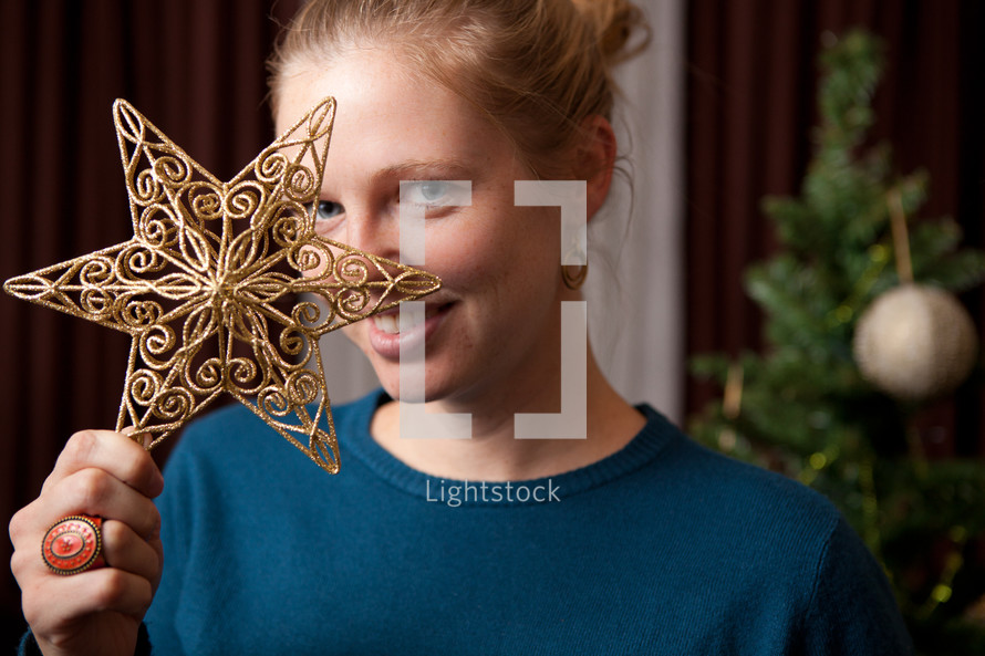 woman holding a star ornament in front of her face
