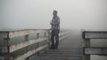 man walking on a boardwalk on a foggy morning