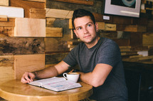 A man sits at a table with an open Bible and cup of coffee.