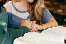 Two women clasp hands as they study the Bible.