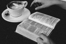 a woman reading a Bible in a coffee shop