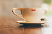 A cup and saucer with a lipstick mark.
