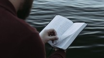 a man reading a Bible over water
