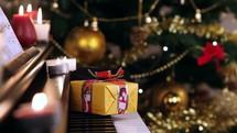 gift on a piano and Christmas tree