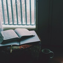 A Bible lays open on an ottoman by a window.