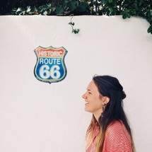 A smiling woman next to a wall with a Route 66 sign.