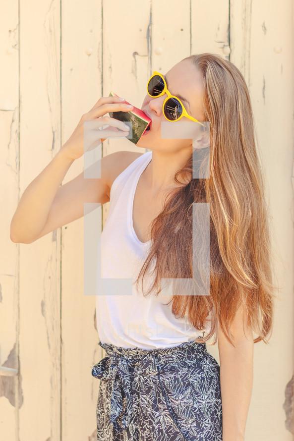 a teen girl eating a watermelon slice