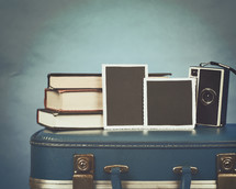 vintage camera and photos on an old suitcase