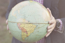 torso of a man holding a globe