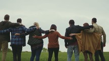 group of friends walking through a field