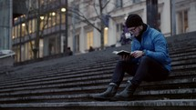 a man sitting on steps in a city reading a Bible in winter