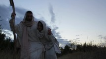 Joseph and a pregnant Mary on the Christmas journey to Bethlehem. Mary stumbles and Joseph helps her up.