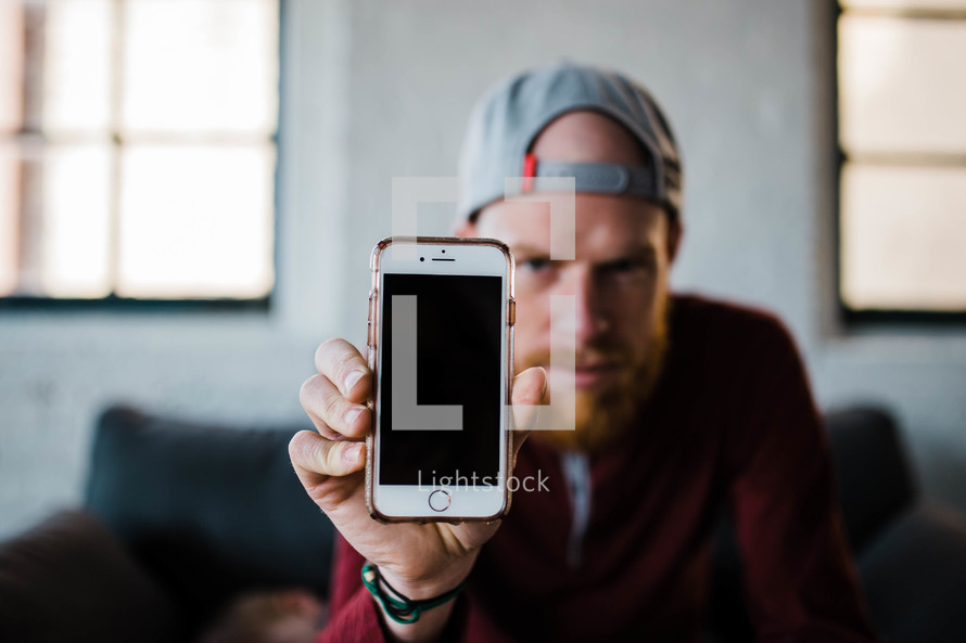 man holding up a blank cellphone screen