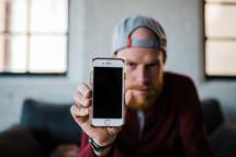 man holding up a blank cellphone screen