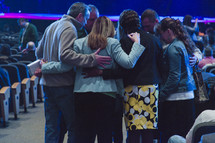 group praying in a circle in a church