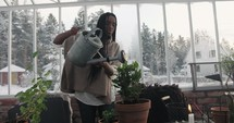 a woman watering plants in a greenhouse