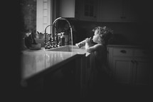 a toddler girl playing in water at the kitchen sink