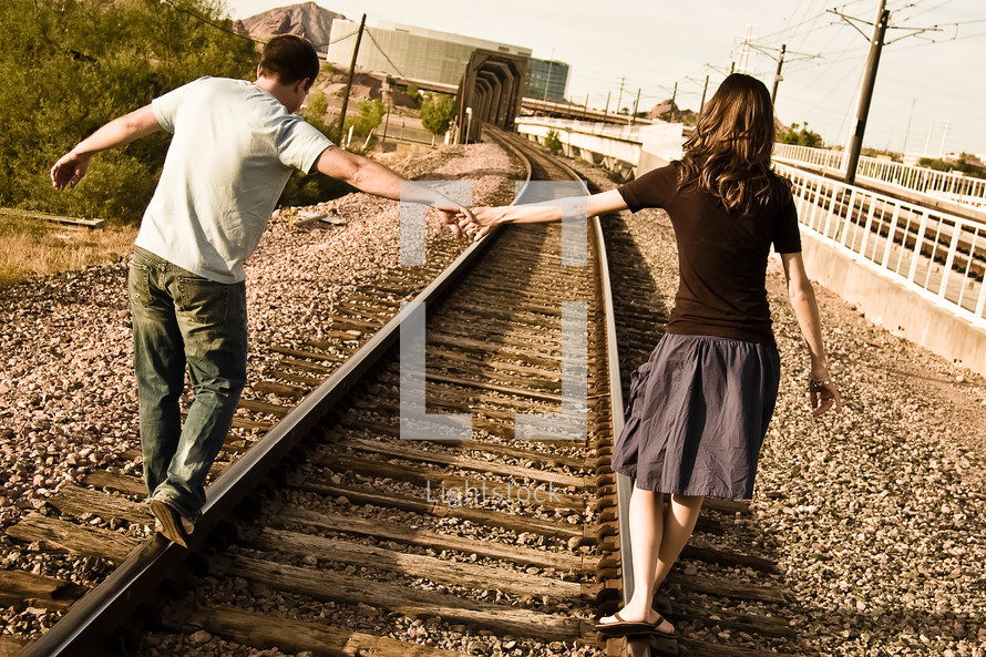 man and a woman walking on railroad tracks holding hands