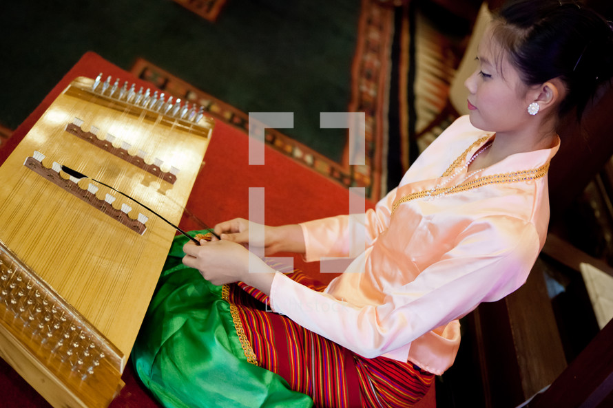 Asian woman dressed ornately kneeling on floor while playing  stringed instrument.