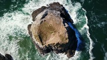 drone flying over a rock formation in the ocean