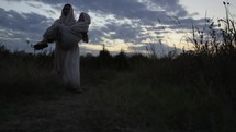 Joseph and Mary on the Christmas journey to Bethlehem. A pregnant Mary falls and Joseph picks her up and carries her part of the way.