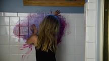 child finger painting on tile