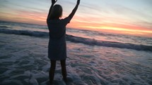 woman with raised hands walking into the ocean