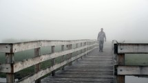 man walking on a boardwalk on a foggy morning