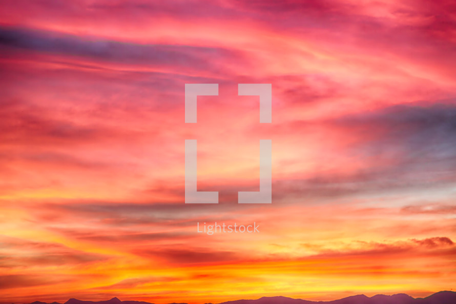 fuchsia, red, purple, pink, orange, and yellow vibrant sky at sunset background