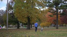 grandfather chasing his granddaughter in a park