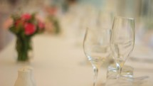 wedding flowers and wine glasses on a table