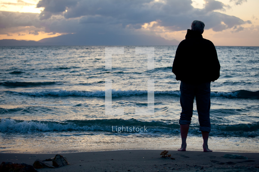 Silhouette of man in jacket with jeans rolled up standing on beach with waves rolling in and cloudy sky at sunset.