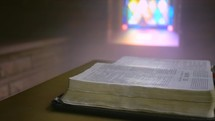 sunlight through a stained glass window shining on a Bible in an old chapel