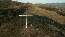man standing next to a cross on a mountaintop