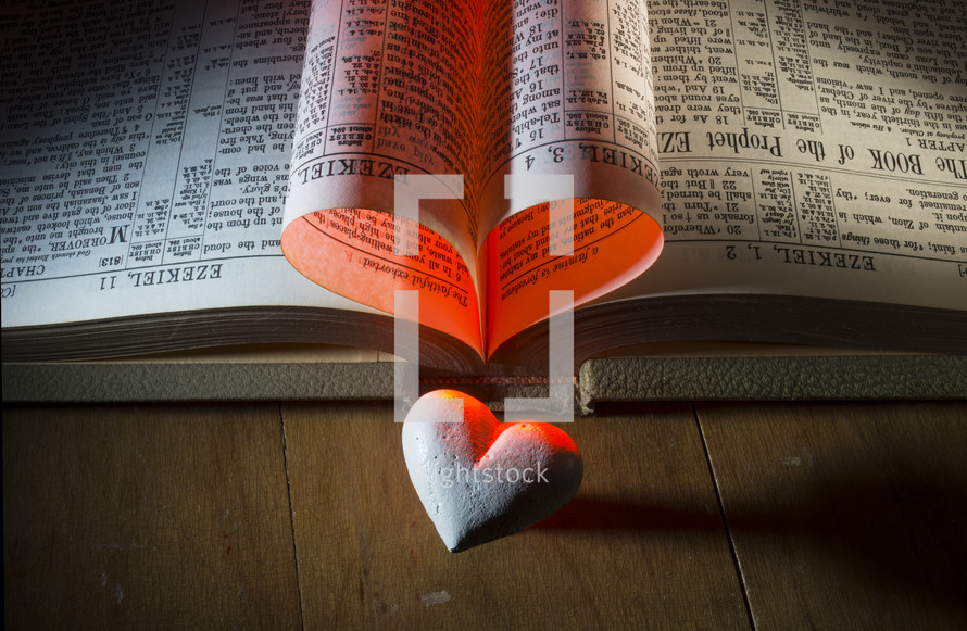 Pages of Bible folded into a heart with a stone heart on a wooden table.