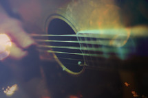 a blurred motion picture of guitar playing with digitally added bokeh and color layers