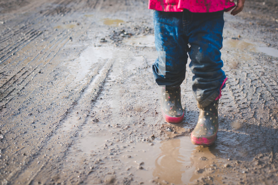 a girl in rain boots walking through a muddy puddle