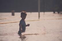 boy child splashing in a lake