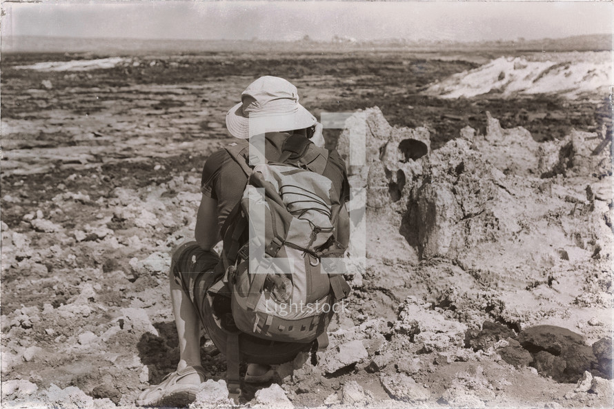 a man with a backpack viewing a volcanic depression