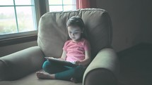 A little girl watches her tablet.