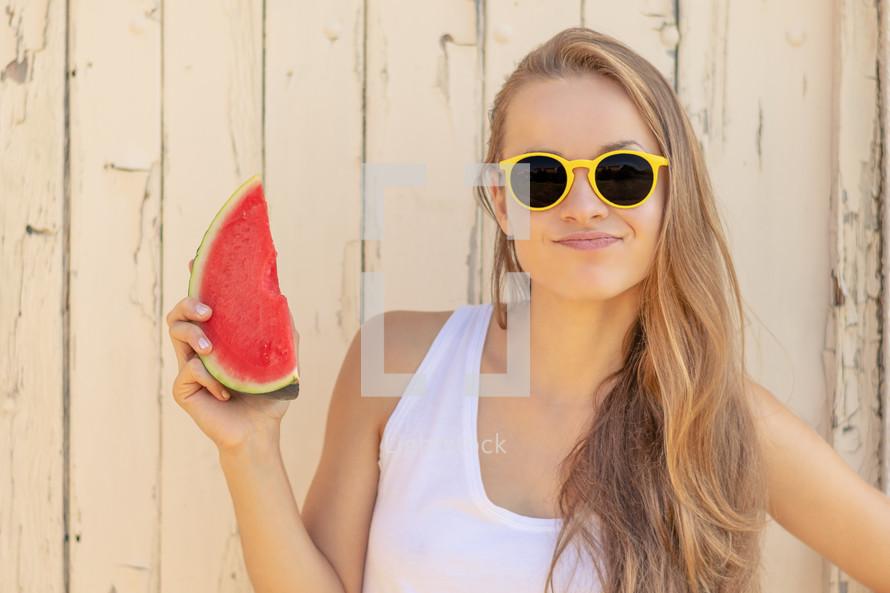 a teen girl holding a watermelon slice