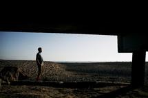 man standing under a pier on a beach