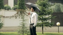 a smiling man standing under an umbrella in the rain