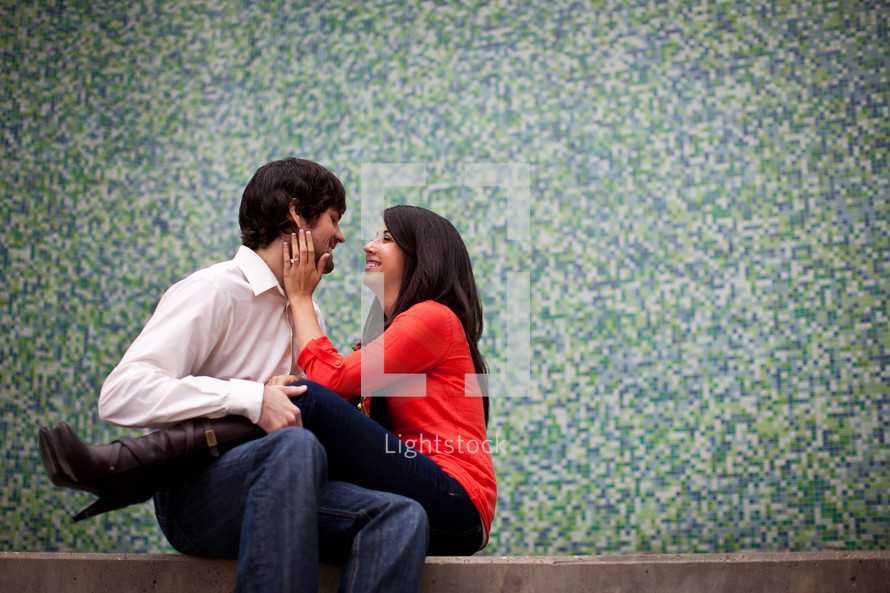 woman sitting in a man's lap with her hands on his face