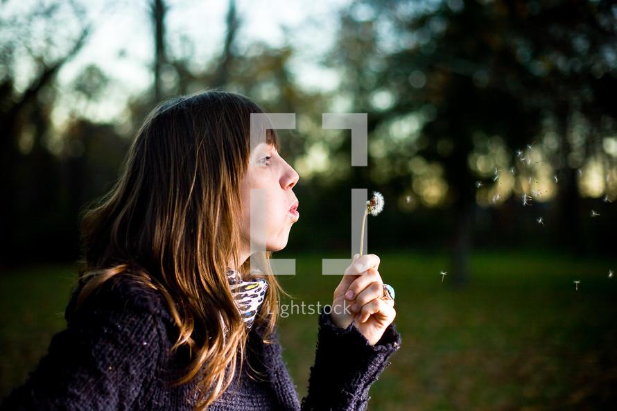 woman blowing a dandy lion
