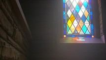 sunlight through a stained glass window in an old chapel