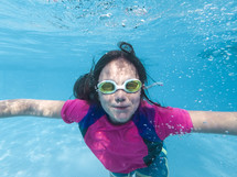 a girl swimming under water