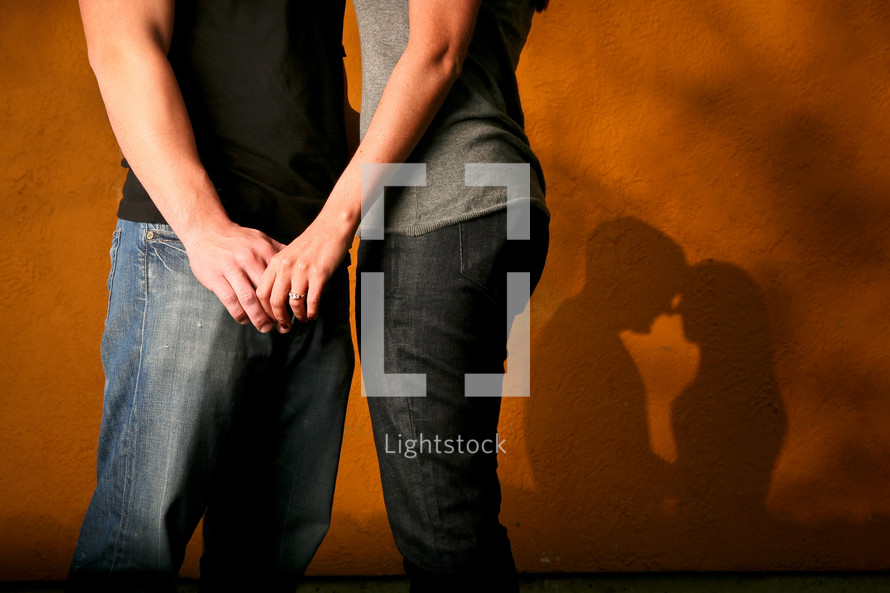 couple holding hands and shadow of a couple